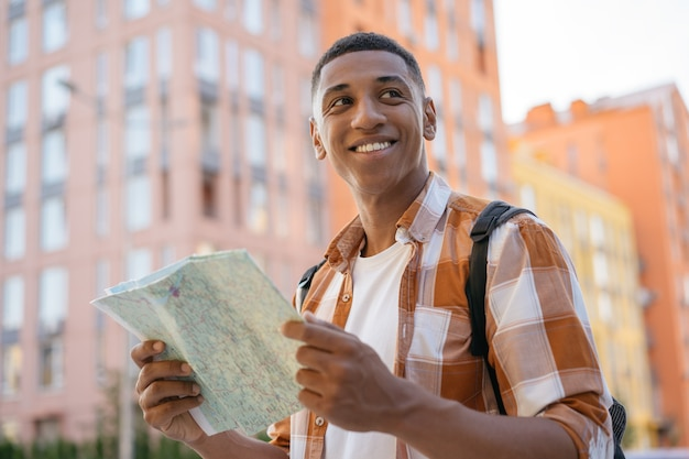 Красивый улыбающийся афро-американский мужчина турист, держащий карту путешествия, поиск пути концепция путешествия