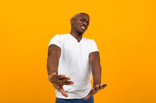 Красивый улыбающийся африканский мужчина в белой футболке, размахивая руками в отрицании на оранжевом фоне.