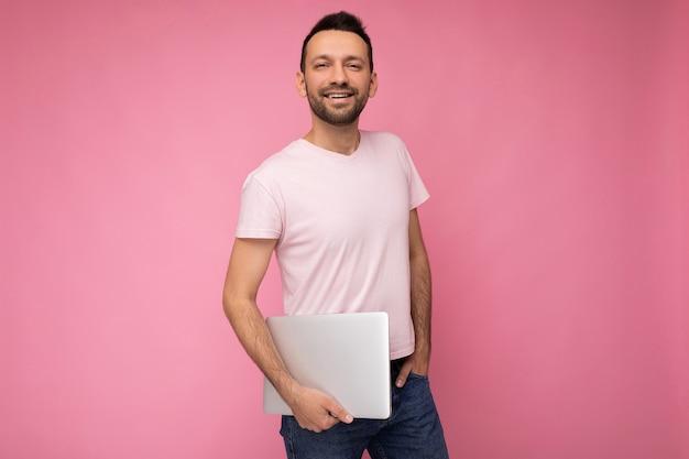 Красивый улыбающийся и счастливый человек, держащий портативный компьютер, смотрящий в камеру в футболке на изолированном розовом