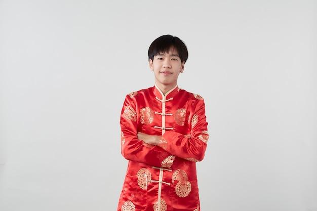 Красивый улыбающийся азиатский мужчина в традиционном восточном костюме изолирован на светло-серой поверхности для концепций китайского нового года
