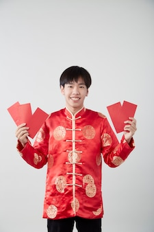Handsome smiling asian man in traditional oriental costume isolated on light gray surface for chinese new year concepts