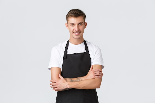 Handsome smiling barista in black apron smiling serving guests in restaurant prepare order for guests standing white wall