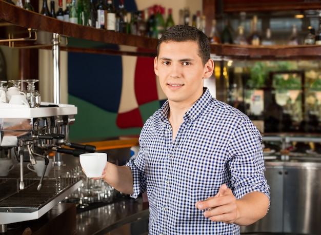 Handsome smiling barista holding a cup of coffee and pointing finger.