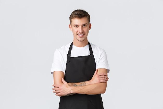 Красивый улыбающийся бариста в черном фартуке улыбается, обслуживая гостей в ресторане, готовит заказ для гостей, стоящих у белой стены