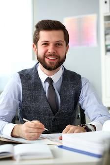 Красивый улыбающийся бородатый клерк человек на рабочем месте в офисе