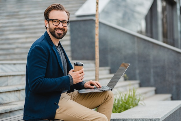 Handsome smiling bearded man in glasses working on laptop