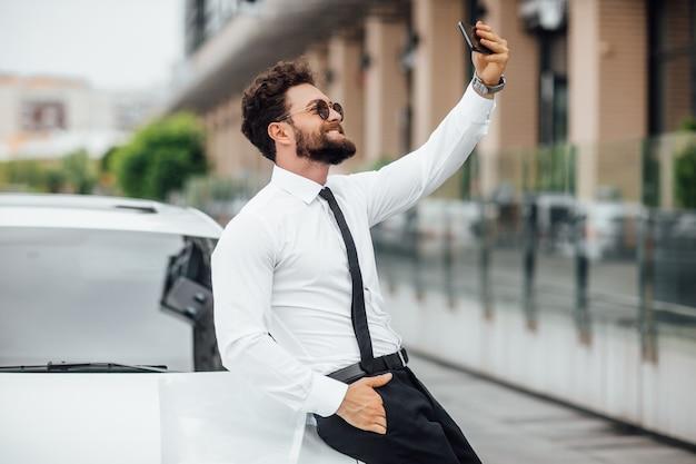 잘생기고, 웃고, 흰 셔츠를 입은 수염난 남자, 도시의 거리에서 야외에서 새 차 근처에서 셀카를 하고 있다