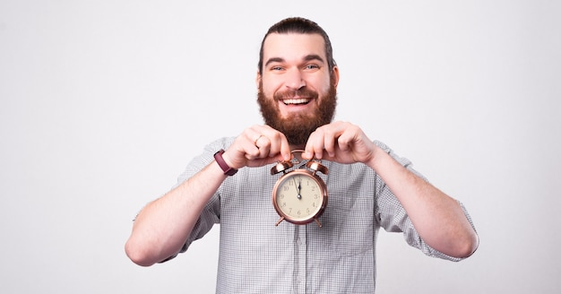Handsome smiling bearded man is holding a cute little clock near his face looking at the camera