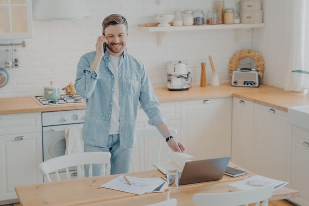 수염이 난 잘생긴 남자는 집에서 식탁에 서서 친구와 휴대전화로 통화하면서 노트북 컴퓨터 작업을 하는 캐주얼 옷을 입고 웃고 있습니다. 프리랜서 및 원격 근무 개념
