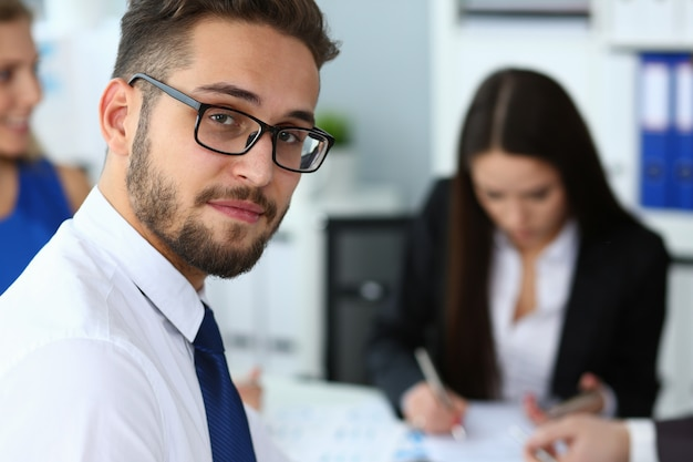 Handsome smiling bearded man working with colleagues in office