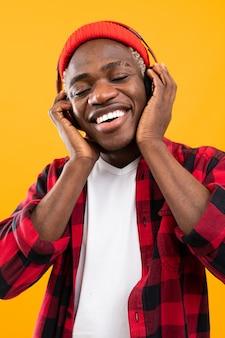 헤드폰을 사용하여 음악을 즐기는 잘 생긴 웃는 흑인 미국 사람