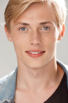 Handsome smiling blond young man wearing casual black t-shirt and jeans jacket on grey wall