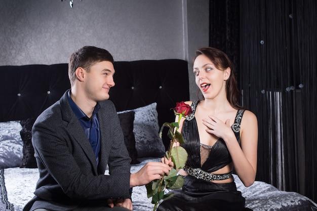 寝室に座っている間、驚きの反応で彼のガールフレンドにバラの花を与えるハンサムな笑顔のボーイフレンド。