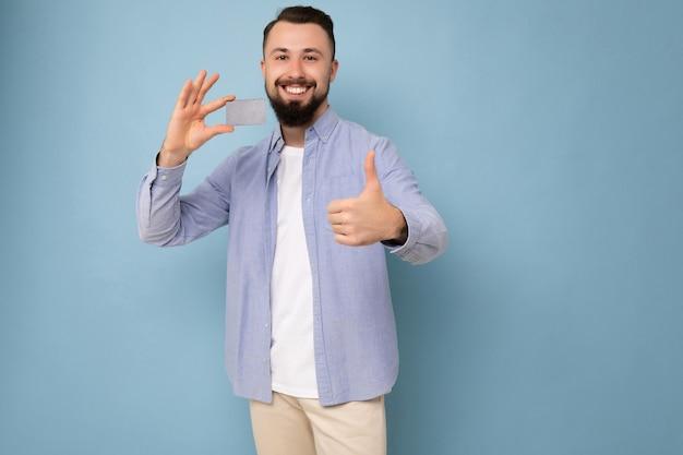 スタイリッシュな青いシャツを着てハンサムな笑顔の黒髪のひげを生やした若い男