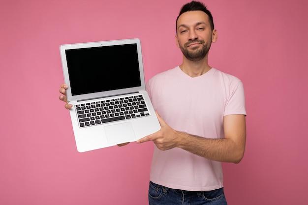 분홍색 벽에 t- 셔츠에 노트북 컴퓨터를 들고 잘 생긴 웃는 brunet 남자.