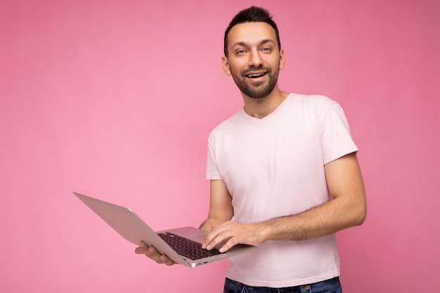Красивый улыбающийся брюнет мужчина, держащий портативный компьютер, глядя на камеру в футболке на изолированном розовом фоне.