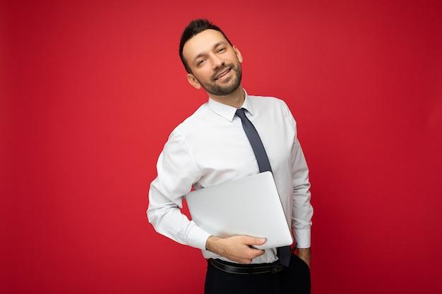 白いシャツと孤立した赤い背景の上のカメラを見てラップトップコンピューターを保持しているハンサムな笑顔の黒髪の男。