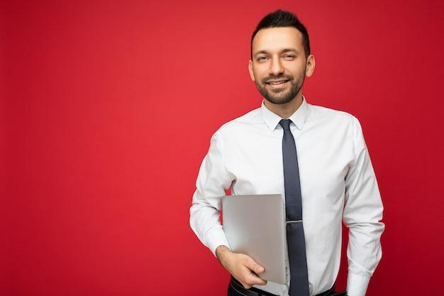 Красивый улыбающийся брюнет мужчина держит портативный компьютер, глядя в камеру в белой рубашке и галстуке