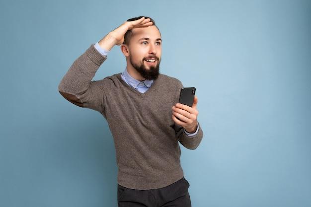 灰色のセーターと青いシャツを着ているハンサムな笑顔のブルネットのひげを生やした男