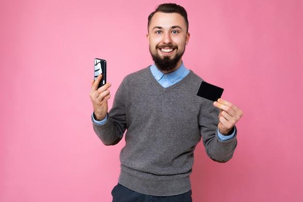 세련 된 회색 스웨터와 파란색 셔츠를 입고 잘 생긴 웃는 갈색 수염 된 젊은 남자