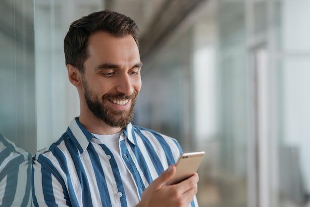 携帯電話通信をオンラインで使用するハンサムな笑顔のビジネスマン