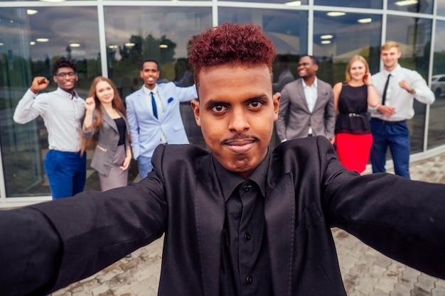 Красивый улыбающийся бизнесмен афро-американский мужчина в стильном костюме и европейский партнер, успешные многорасовые деловые мужчины и женская команда, делающие селфи вместе на камеру