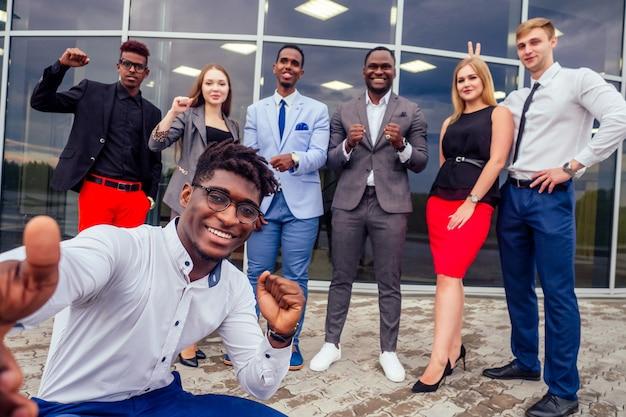 Афро-американский мужчина красивый улыбающийся бизнесмен в стильном костюме и успешный европейский партнер.