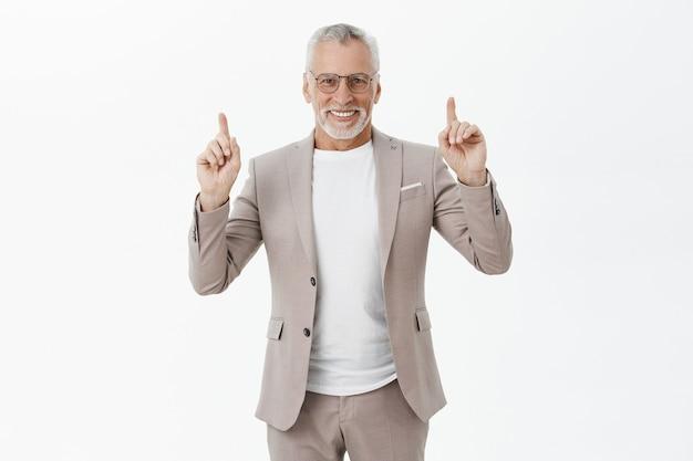 眼鏡とスーツのハンサムな笑顔のビジネスマンが指を上に向けて、広告を表示