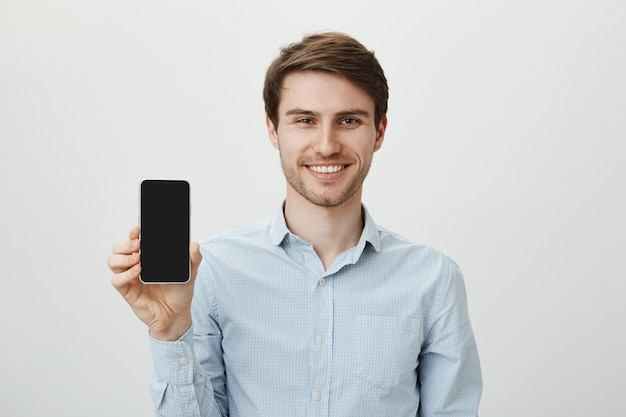 ハンサムな笑みを浮かべてビジネスマンがモバイルアプリケーションを促進し、スマートフォンのディスプレイを表示