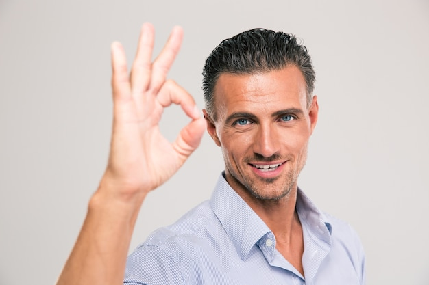 Красивый улыбающийся бизнесмен показывает знак ок пальцами над серым пространством