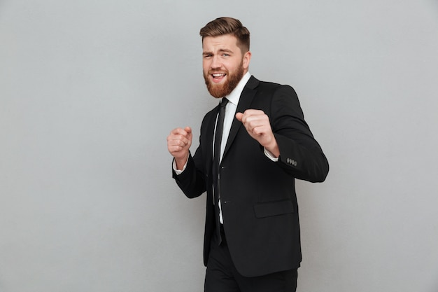 Handsome smiling businessman in suit posing