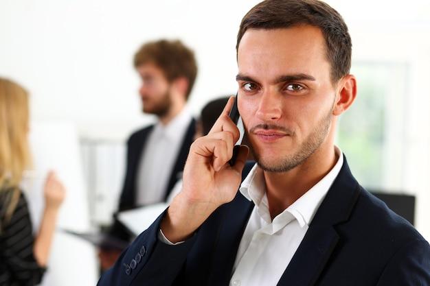 ハンサムな笑顔のビジネスマンが携帯電話で話します