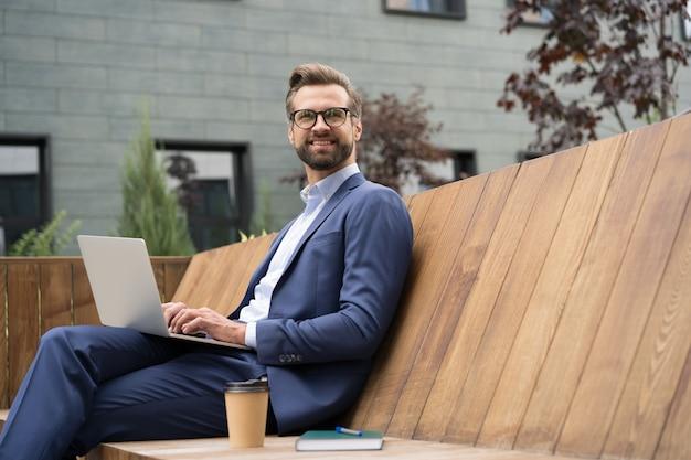 ラップトップコンピューターを使用してハンサムな笑顔のビジネスマンオンラインで作業しているひげを生やしたフリーランサー