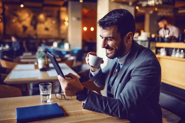 ハンサムな笑みを浮かべて白人のひげを生やした実業家スーツのカフェに座って、コーヒーを飲みながら、タブレットを使用しています。