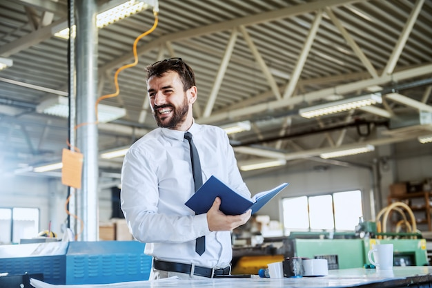 Handsome smiling caucasian bearded graphic engineer holding notebook while standing in printing shop.
