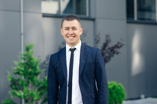 Handsome smiling confident businessman portrait. modern businessman. confident young man in suit looking away while standing outdoors with cityscape in the background.