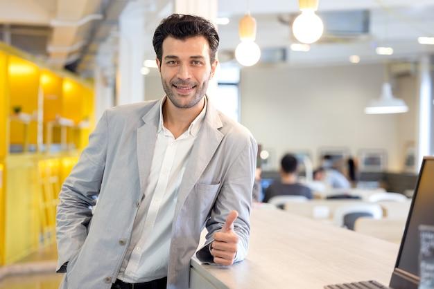 Красивый улыбающийся уверенный портрет бизнесмена, оставайтесь голодными до успеха в высокотехнологичном офисе