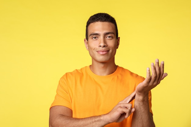 Handsome smiling and confident man in yellow t-shirt, measuring own pulse