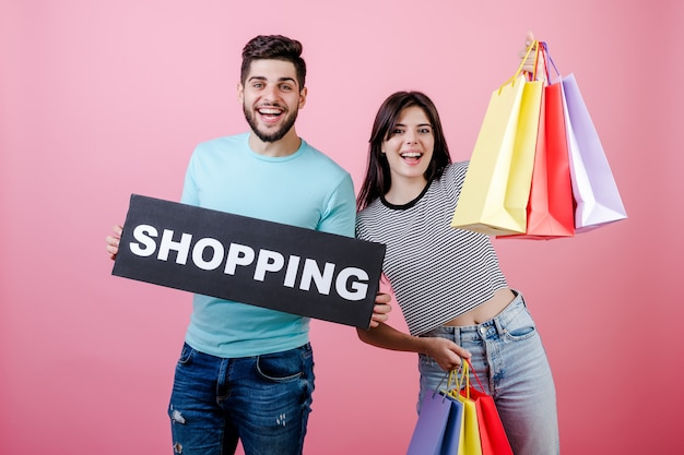 Handsome smiling couple guy and girl with shopping sign and colorful bags