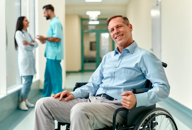 A handsome smiling elderly disabled person in a wheelchair sits in the middle of a clinic corridor with doctors behind him.