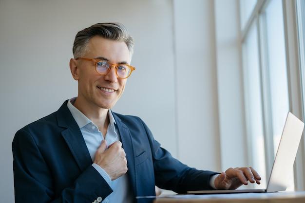 Handsome smiling freelancer in stylish eyeglasses using laptop