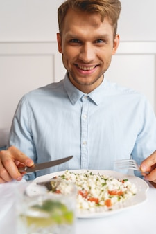 신선한 샐러드와 함께 테이블에 앉아 있는 동안 포크와 나이프를 들고 웃는 잘 생긴 신사