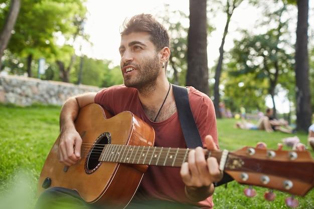 公園でギターを弾き、草の上に座って、のんきな週末を過ごしてハンサムな笑みを浮かべて男