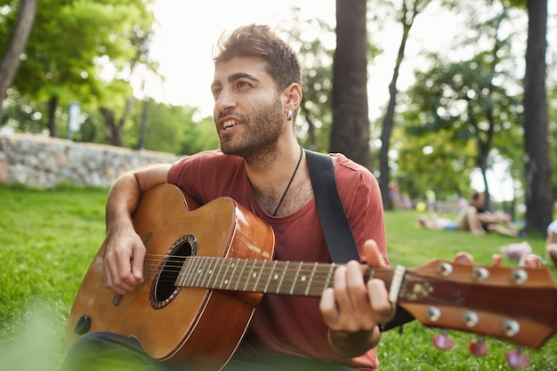 Handsome smiling guy playing guitar in park, sitting on grass, having carefree weekend