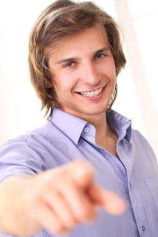 Handsome smiling guy pointing at camera