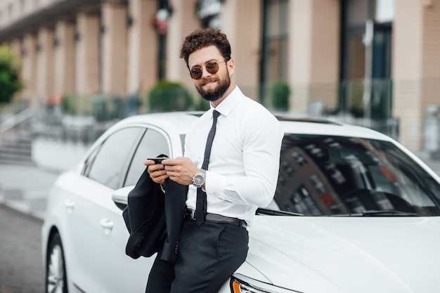 Красивый, улыбающийся, счастливый, бородатый бизнесмен в костюме использует смартфон и стоит возле своей новой белой машины на улице возле современного офисного центра