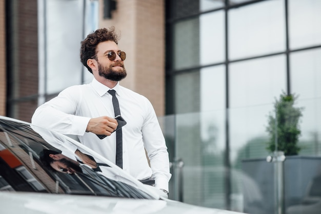 Handsome, smiling, happy, bearded businessman is using his mobile phone and standing near his car outdoors on the streets