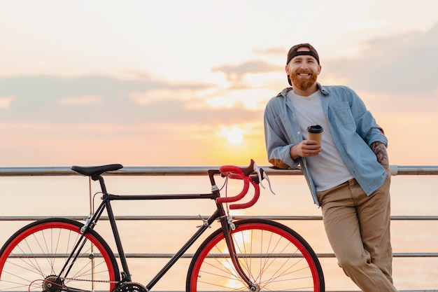 ハンサムな笑顔の幸せなヒップスタースタイルのひげを生やした男は、コーヒーを飲み、健康的なアクティブなライフスタイルの旅行者、海沿いの朝の日の出に自転車でデニムシャツとキャップを身に着けています