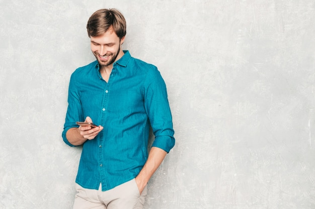 Handsome smiling hipster lumbersexual businessman model wearing casual jeans shirt clothes.