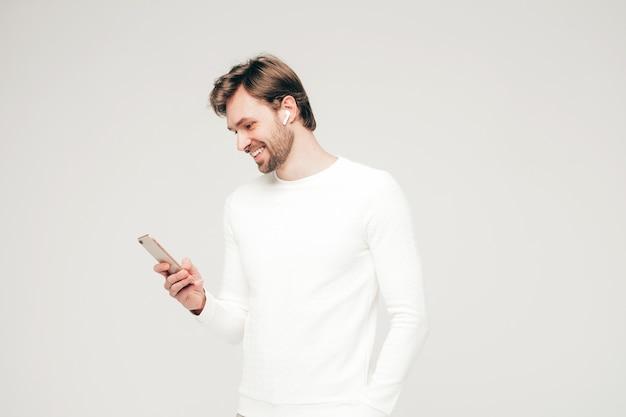 白いカジュアルなセーターとズボンを身に着けているハンサムな笑顔の流行に敏感な腰痛のビジネスマンモデル